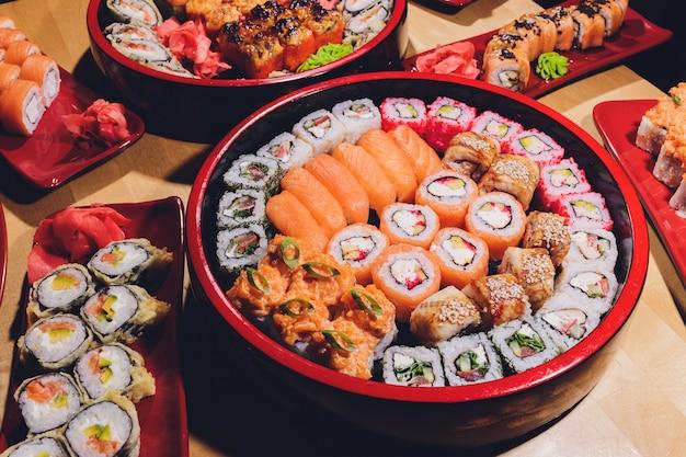Foto da bandeja fresca do sushi do maki com muita variedade. foco seletivo no meio do prato. Foto Premium