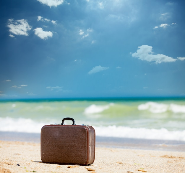 Foto da mala marrom bonita no fundo maravilhoso praia ensolarada Foto Premium