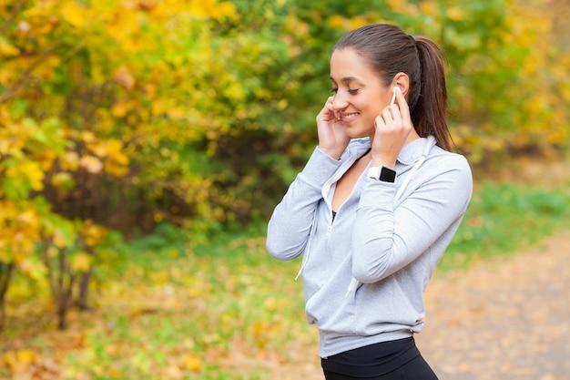 Foto da mulher alegre fitness 30 anos no sportswear tocando bluetooth earpod e segurando o telefone móvel, enquanto descansava no parque verde Foto Premium