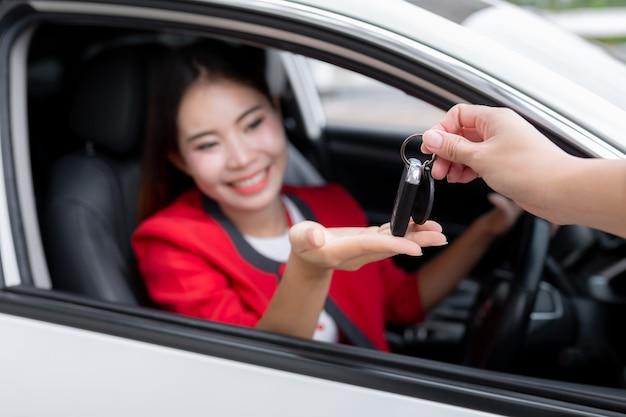 Foto da mulher nova feliz da raça misturada que mostra a chave a seu carro novo. conceito para o aluguer de automóveis. Foto Premium