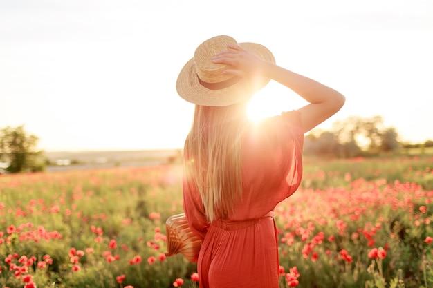 Foto da parte de trás de uma jovem inspirada segurando o chapéu de palha e olhando para o horizonte. conceito de liberdade. cores quentes do sol. campo de papoula. Foto gratuita