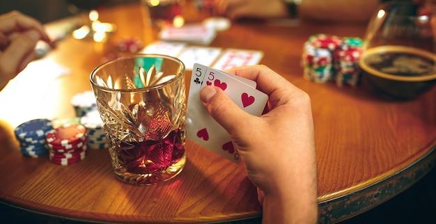 Foto da vista lateral de amigos do sexo masculino e feminino sentados à mesa de madeira. homens e mulheres jogando jogo de cartas. mãos com close-up de álcool. Foto gratuita