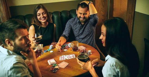 Foto da vista lateral de amigos sentados à mesa de madeira. amigos se divertindo enquanto jogam o jogo de tabuleiro. Foto gratuita