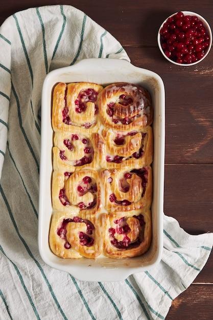 Foto da vista superior de deliciosos pastéis de caracol de groselha em uma forma sobre uma mesa de madeira Foto gratuita