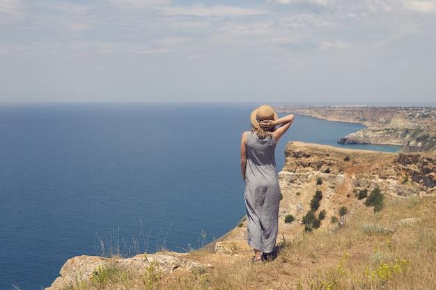Foto das costas de uma jovem em um vestido elegante admirando a vista deslumbrante enquanto está de pé na beira do topo da montanha, de frente para o vasto oceano azul, segurando um chapéu de palha para mantê-lo na cabeça por causa do vento Foto gratuita