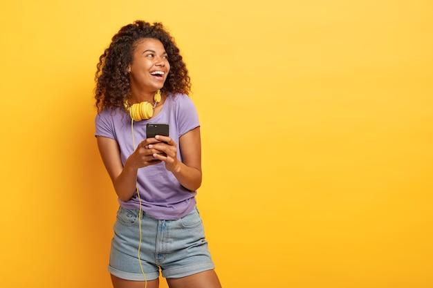 Foto de adolescente sorridente com corte de cabelo afro, usa smartphone para ouvir música na playlist, usa fones de ouvido, parece positivamente de lado Foto gratuita
