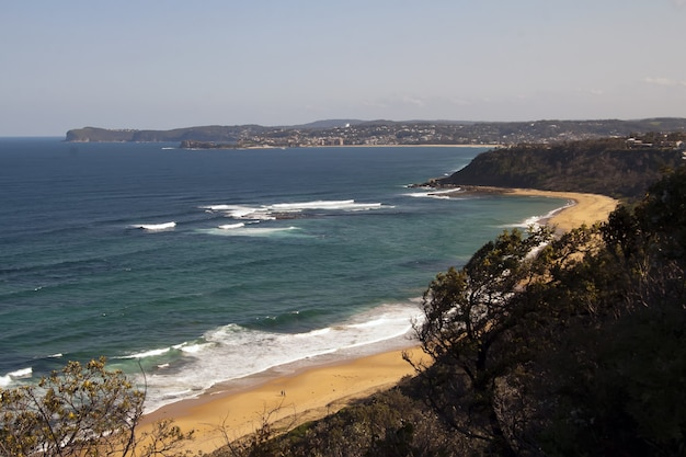 Foto de alto ângulo da costa do oceano com uma pequena praia de areia Foto gratuita