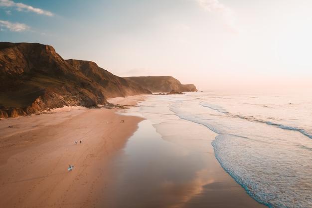 Foto de alto ângulo das ondas do mar chegando à praia ao lado de penhascos rochosos sob o céu claro Foto gratuita