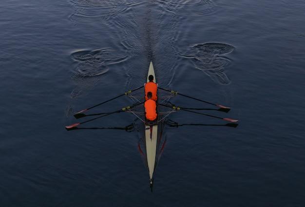 Foto de alto ângulo de duas pessoas remando em um barco no meio do mar Foto gratuita