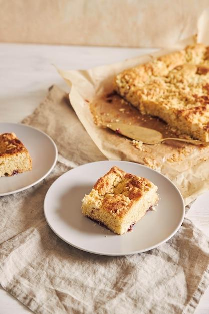 Foto de alto ângulo de um pedaço do delicioso bolo de folha de jerry crumble em uma mesa de madeira branca Foto gratuita