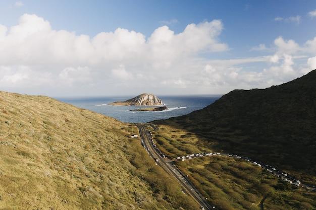 Foto de alto ângulo de um vale de montanha com uma pequena ilha em mar aberto Foto gratuita