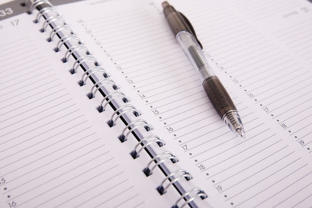 Foto de alto ângulo de uma caneta em um caderno aberto Foto gratuita