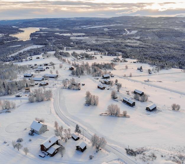 Foto de alto ângulo de uma cidade coberta de neve, rodeada por florestas e um lago sob um céu nublado Foto gratuita