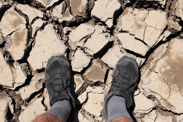 Foto de alto ângulo de uma pessoa em pé no chão lamacento seco e rachado Foto gratuita
