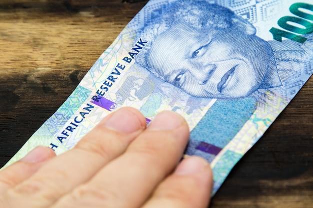 Foto de alto ângulo de uma pessoa segurando dinheiro sobre uma superfície de madeira Foto gratuita