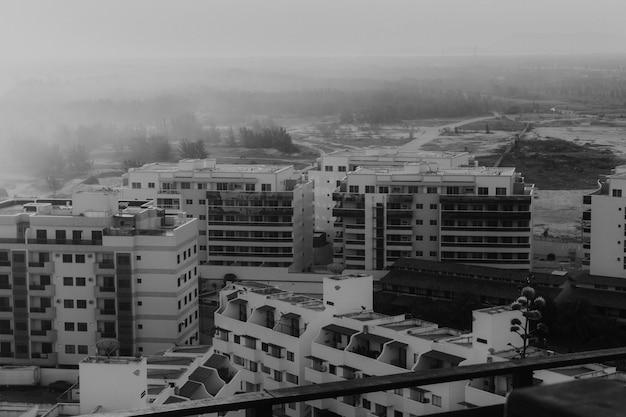 Foto de alto ângulo em tons de cinza dos edifícios na praia, capturada no pôr do sol com neblina Foto gratuita