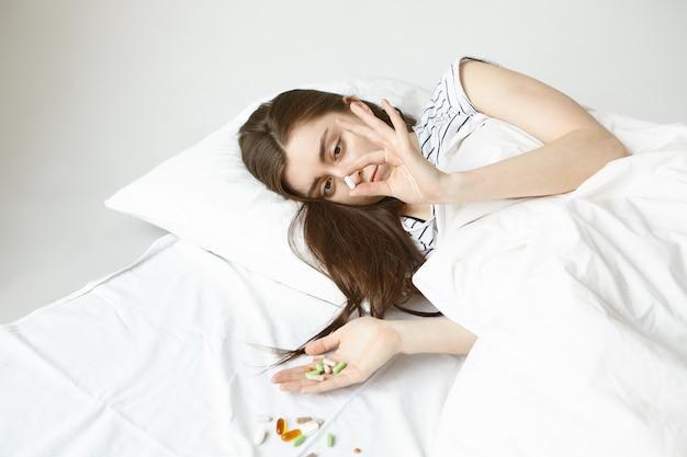 Foto de aluna de cabelos escuros passando o dia na cama, tentando se recuperar da gripe, segurando um monte de pílulas coloridas nas mãos e derramada em um lençol branco, escolhendo qual delas deve ficar boa Foto gratuita