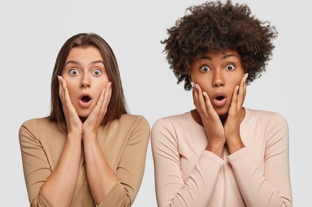 Foto de amigas inter-raciais espantadas mantendo ambas as mãos nos rostos, ofegando de admiração, ficando próximas uma da outra Foto gratuita