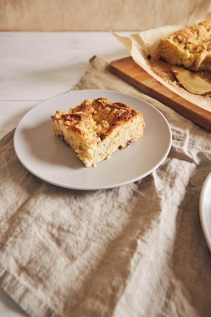 Foto de ângulo superior de um pedaço do delicioso bolo de folha de jerry crumble em uma mesa de madeira branca Foto gratuita