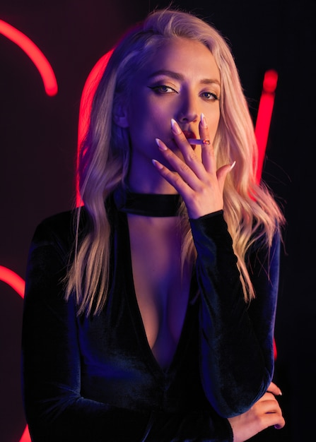 Foto de arte moda de modelo elegante em maiô preto sedutor com holofotes de clube colorido de luz néon Foto Premium