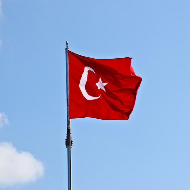 Foto de baixo ângulo da bandeira da turquia sob um céu claro Foto gratuita