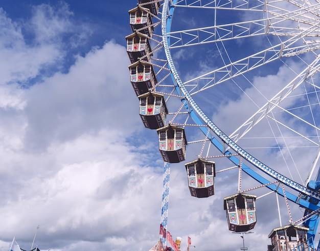 Foto de baixo ângulo de um carrossel circular girando sob um céu cheio de nuvens Foto gratuita
