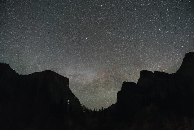 Foto de baixo ângulo de um cenário montanhoso sob o céu noturno mágico Foto gratuita