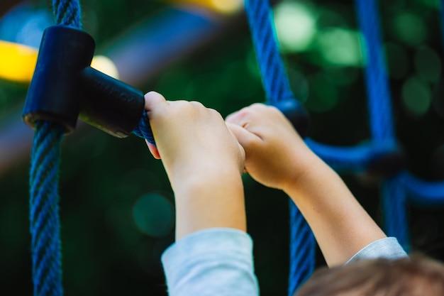 Foto de baixo ângulo de uma criança segurando um brinquedo de escalada azul no parquinho de um parque Foto gratuita