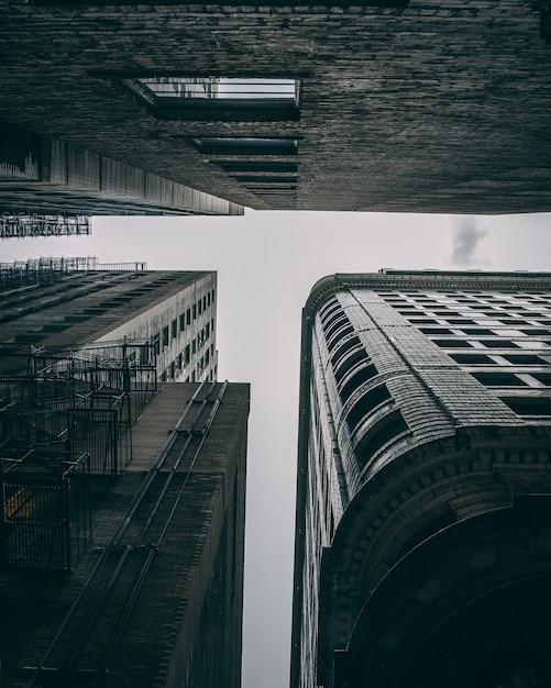 Foto de baixo ângulo dos edifícios altos com escadas de metal em um dia sombrio Foto gratuita