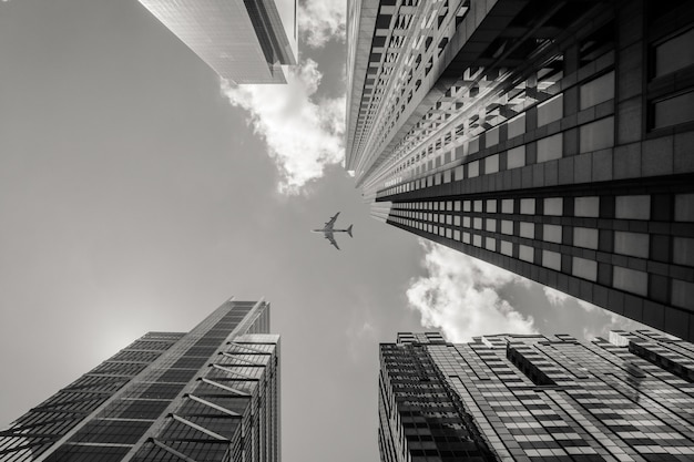 Foto de baixo ângulo em escala de cinza de um avião voando acima de prédios altos Foto gratuita