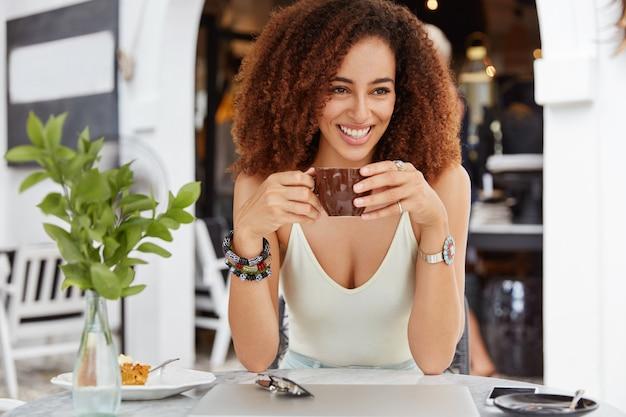 Foto de bela sorridente mulher de pele escura com cabelo encaracolado afro bebidas expresso no café tem uma expressão positiva. Foto gratuita