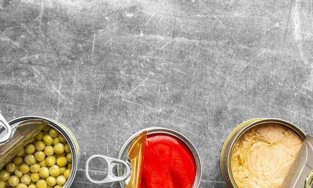 Foto de cima de três latas de conservas alinhadas na parte inferior da imagem aberta de pimenta vermelha, atum claro e ervilhas com superfície cinza e luz natural suave Foto Premium