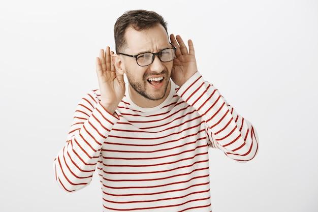 Foto de cintura para cima de um cara caucasiano confuso questionado de óculos escuros Foto gratuita