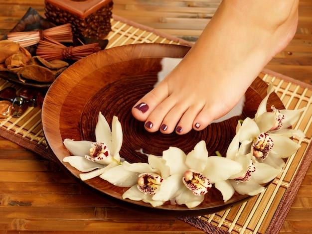 Foto de close de um pé feminino em um salão de beleza em procedimento de pedicure Foto gratuita