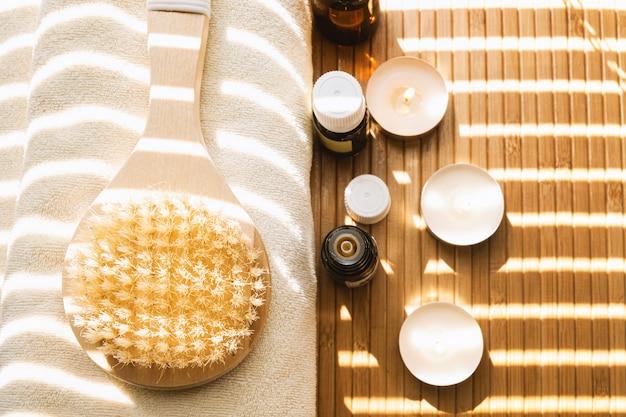 Foto de close-up de escova de banho com óleos essenciais e velas. conceito de spa. Foto gratuita