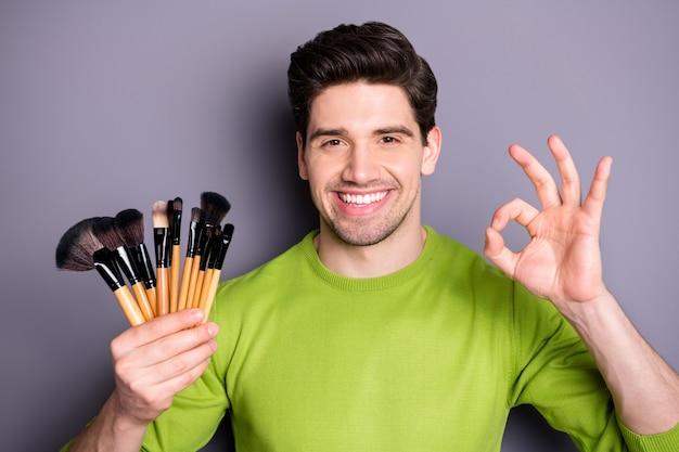 Foto de close-up de homem confiante e legal, trabalhador visagista, segurar borlas, escovas, mostrar sinal de bom, sugerir ótima festa, maquiagem, maquiagem, vestir, camisola verde Foto Premium