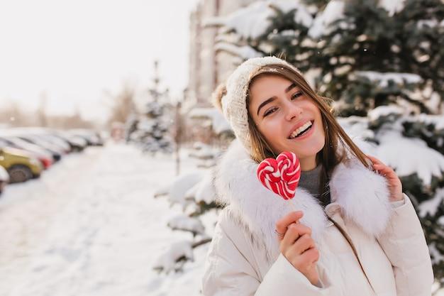 Foto de close-up de mulher de cabelos compridos encantadora, caminhando na rua de neve com pirulito. mulher muito sorridente com chapéu de malha, aproveitando o fim de semana de inverno ao ar livre. Foto gratuita