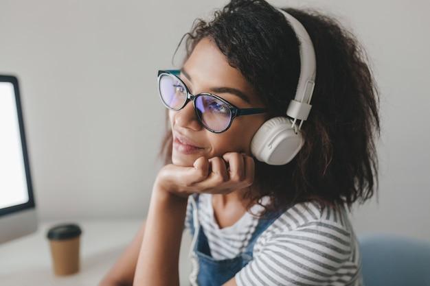 Foto de close-up de uma garota sonhadora com pele castanha-clara pensando em algo agradável enquanto ouve música Foto gratuita