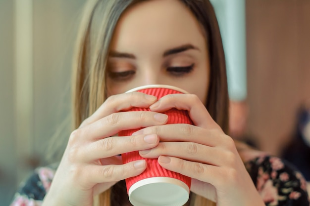 Foto de close-up de uma jovem sentada em um café tomando café Foto Premium