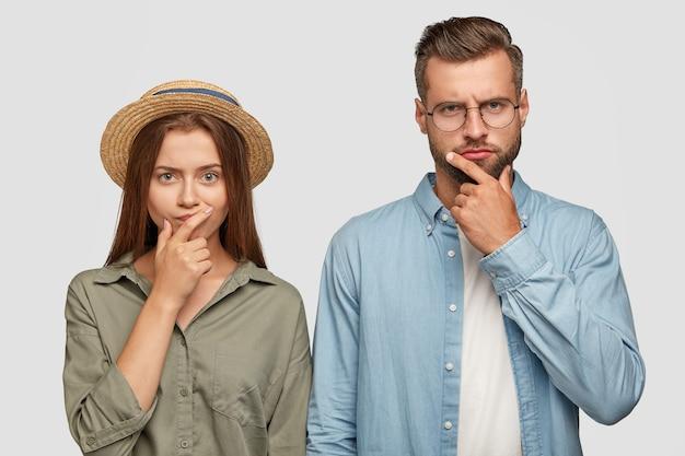 Foto de colegas de trabalho confusos, do sexo feminino e masculino, mantendo as mãos no queixo Foto gratuita