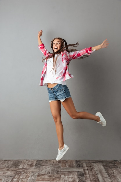 Foto de corpo inteiro da bela jovem em fones de ouvido, ouvindo música e pulando Foto gratuita