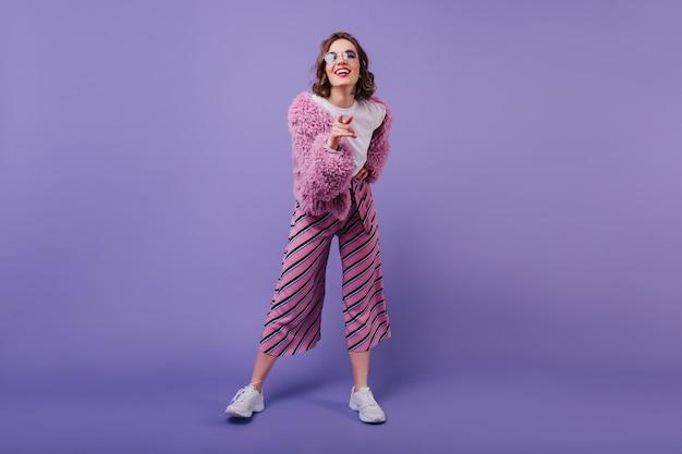 Foto de corpo inteiro da encantadora mulher encaracolada em calças cor de rosa expressando felicidade. foto interna de garota caucasiana rindo usa tênis branco. Foto gratuita