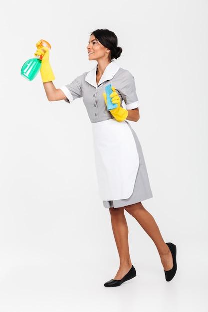 Foto de corpo inteiro da jovem morena mais em luvas de proteção uniformes e amarelas, pulverizando o limpador na janela Foto gratuita