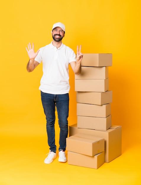 Foto de corpo inteiro de entregador entre caixas sobre amarelo isolado, contando sete com os dedos Foto Premium