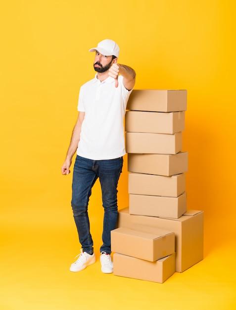 Foto de corpo inteiro de entregador entre caixas sobre amarelo isolado mostrando o polegar para baixo com expressão negativa Foto Premium