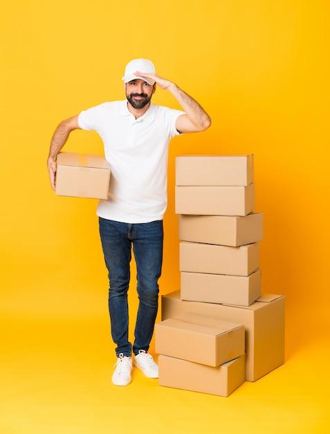 Foto de corpo inteiro de entregador entre caixas sobre amarelo isolado olhando longe com a mão para procurar algo Foto Premium