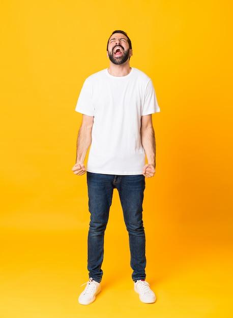Foto de corpo inteiro de homem com barba sobre amarelo isolado gritando para a frente com a boca aberta Foto Premium