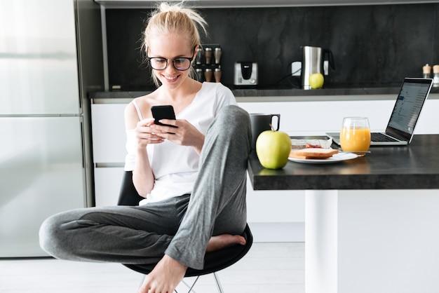 Foto de corpo inteiro de jovem focada usando smartphone enquanto está sentado na cozinha Foto gratuita