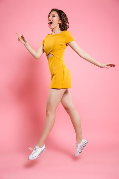 Foto de corpo inteiro de menina bonita com maquiagem de lábios vermelhos, apontando com o dedo, olhando de lado ao saltar sobre rosa Foto gratuita