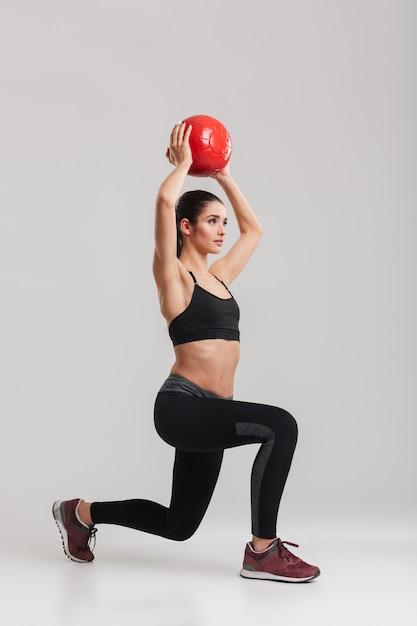 Foto de corpo inteiro de sério desportista concentrada, olhando de lado e fazendo estocada exercícios levantando bola de fitness, isolado sobre a parede cinza Foto Premium